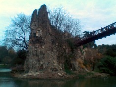 A tall, craggy rock promontory, covered in trees, rises almost vertically out of a green lake. To the right a bridge leads across to it